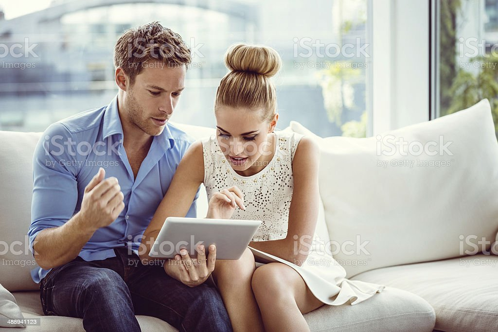 Couple using a digital tablet Young couple sitting on sofa in an apartment and using digital tablet together. 25-29 Years Stock Photo