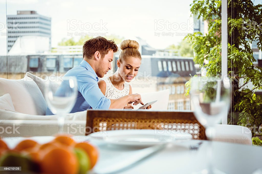 Couple using a digital tablet Young couple sitting on sofa in their penthouse and using digital tablet together. 25-29 Years Stock Photo