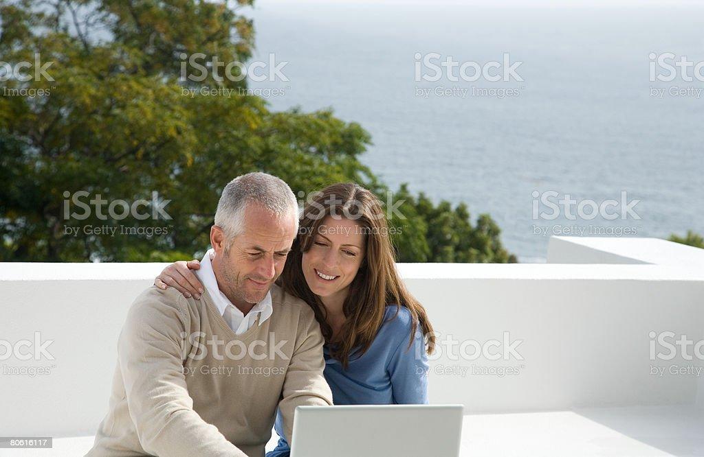 Um casal usando um computador portátil foto de stock royalty-free