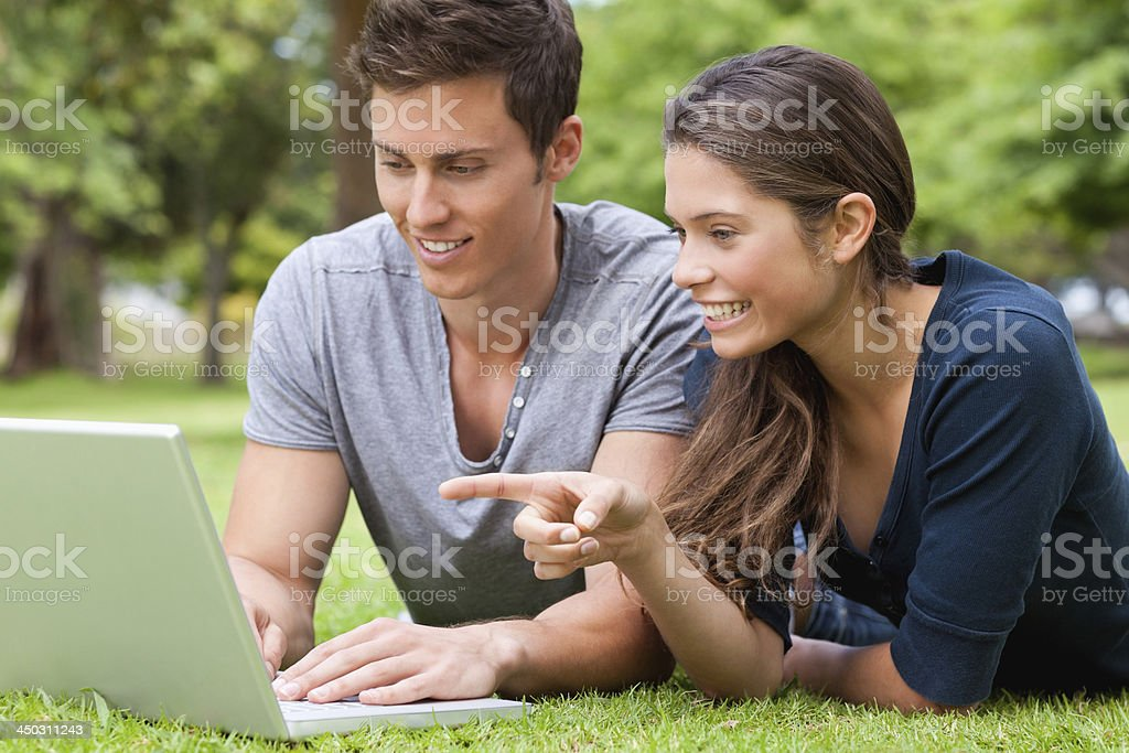 Couple using a laptop while lying on the tummy royalty-free stock photo