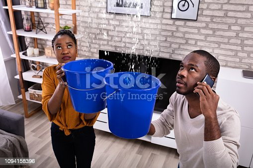 Couple Using Bucket For Collecting Water Leakage From Ceiling And Calling Plumber On Cellphone