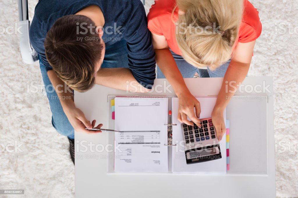 Couple Using Calculator For Calculating Invoice stock photo