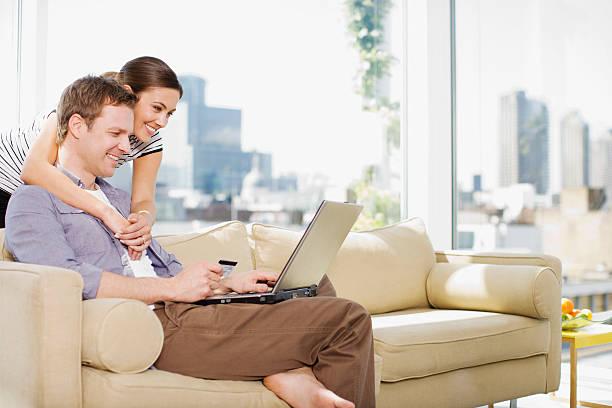 paar mit kreditkarte für den kauf von waren auf internet - sofa online kaufen stock-fotos und bilder