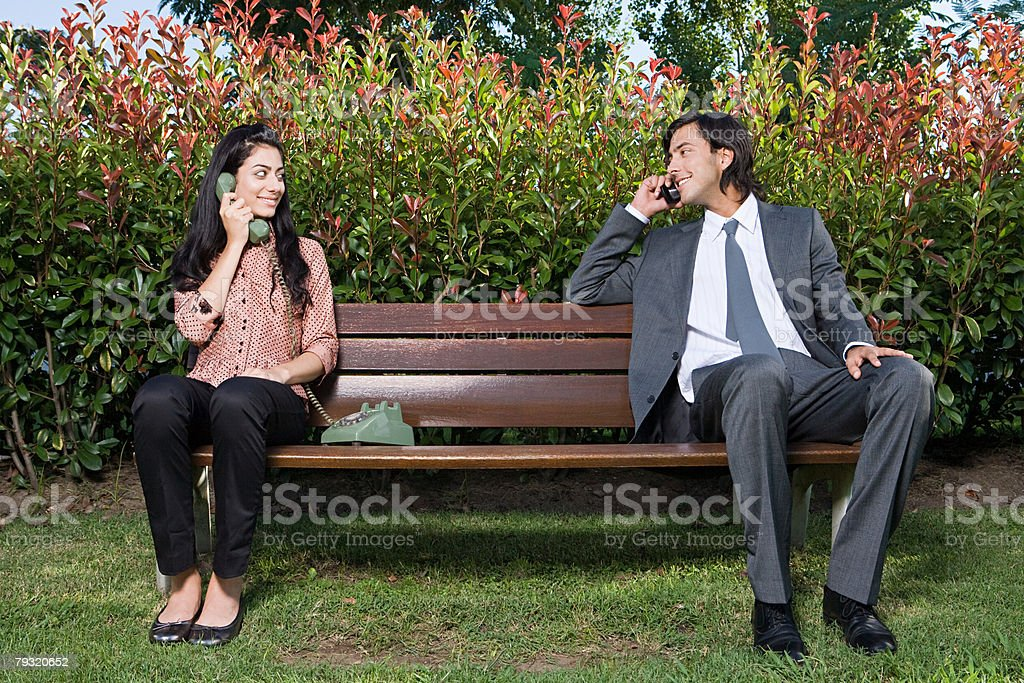 Couple using different phones on bench 免版稅 stock photo