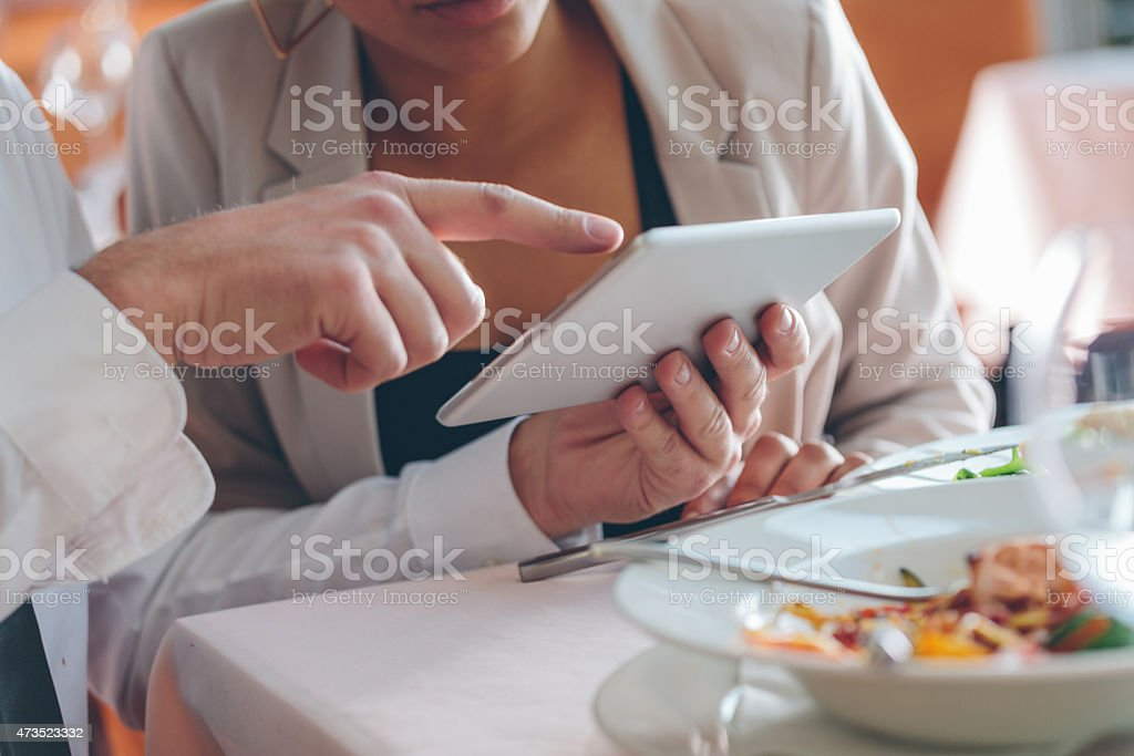 Couple using digital tablet at lunch Businesswoman and businessman having lunch in the restaurant, using a digital tablet together. Close up of hands. Unrecognizable person. Plate on the table. 2015 Stock Photo