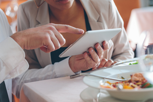 Couple Using Digital Tablet At Lunch Stock Photo - Download Image Now