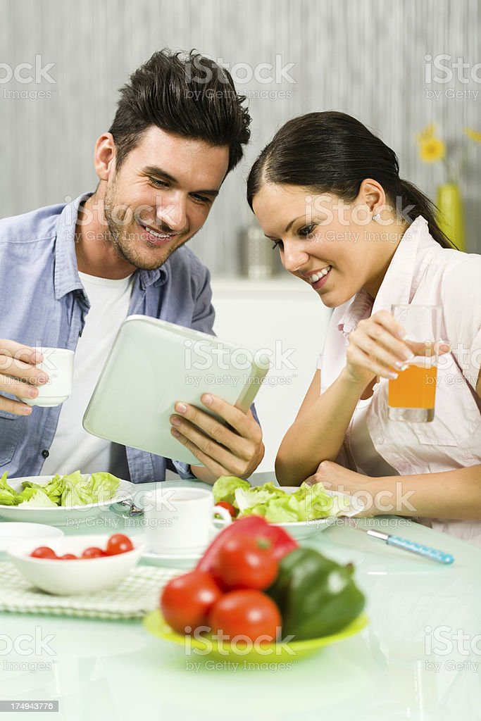 Couple using digital tablet during lunch royalty-free stock photo