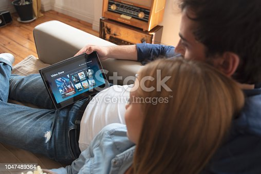 istock Couple using digital tablet for watching movie on VOD service 1047489364