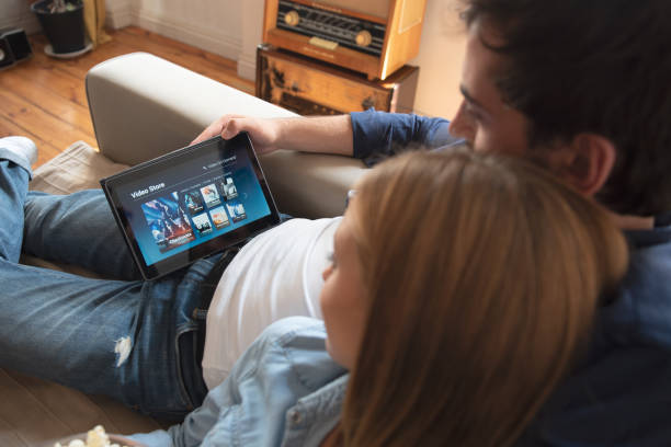 couple using digital tablet for watching movie on vod service - home show stock photos and pictures