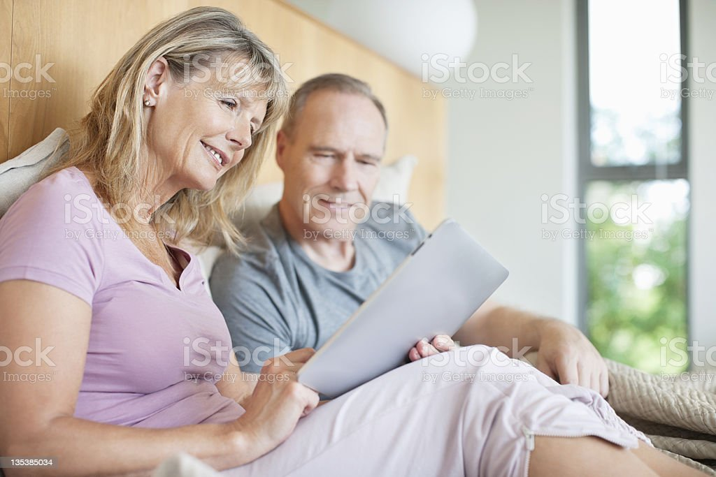 Couple using digital tablet in bed royalty-free stock photo