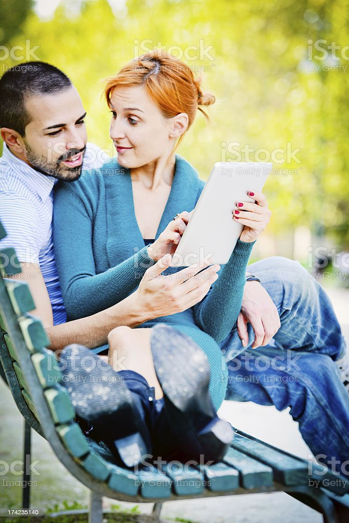 Couple using digital tablet in park royalty-free stock photo