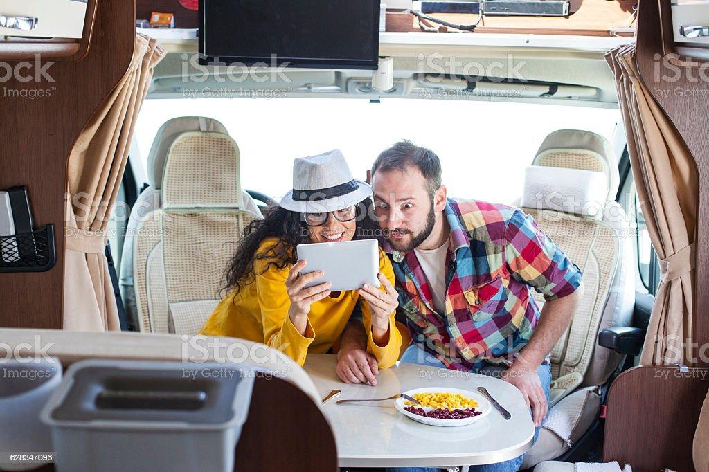 Couple using digital tablet inside of caravan stock photo