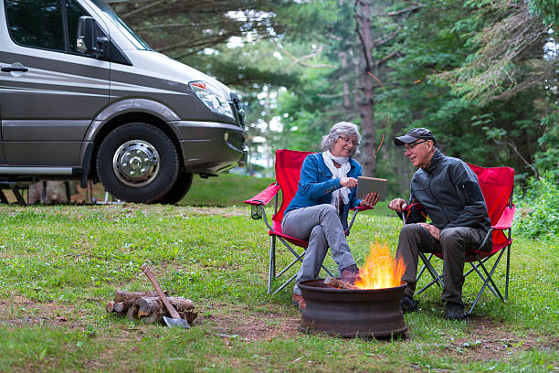 Couple using digital tablet near campfire stock photo