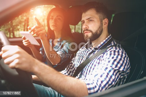 couple using gps on tablet compter to navigate in car on holiday.