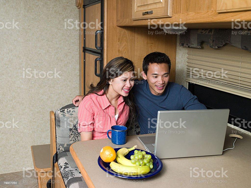 Casal usando computador portátil em Caravana foto de stock royalty-free
