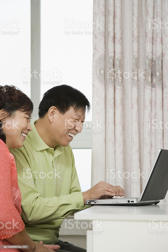 Couple using laptop, smiling foto de stock libre de derechos
