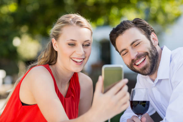 Couple using mobile phone in a restaurant Happy couple using mobile phone in a restaurant age contrast stock pictures, royalty-free photos & images