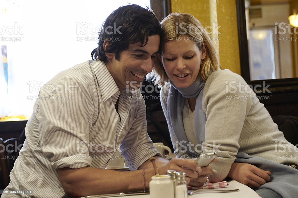 Couple using mobile phone sitting in cafe foto de stock royalty-free