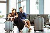 Couple using mobile phones while waiting at airport