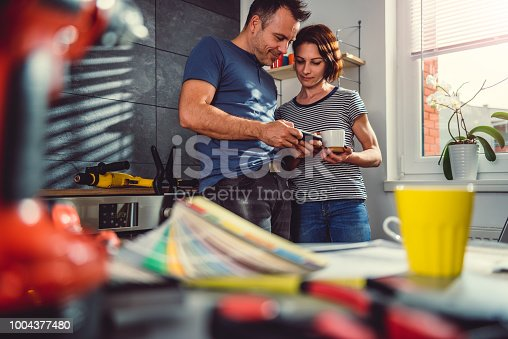 istock Couple using smart phone in kitchen during renovation 1004377480