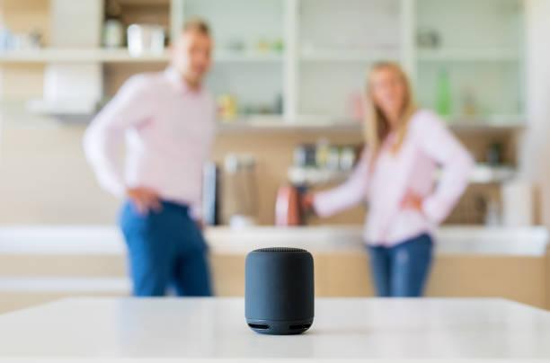 Casal usando alto-falante inteligente em casa - foto de acervo
