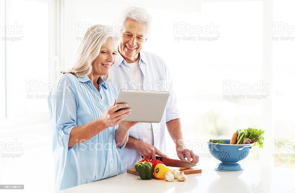 Couple Using Tablet Computer In Kitchen Happy senior couple checking out recipe from tablet computer while cooking in kitchen. Horizontal shot. 60-69 Years Stock Photo