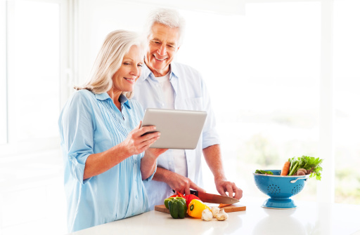 Couple Using Tablet Computer In Kitchen Stock Photo - Download Image Now