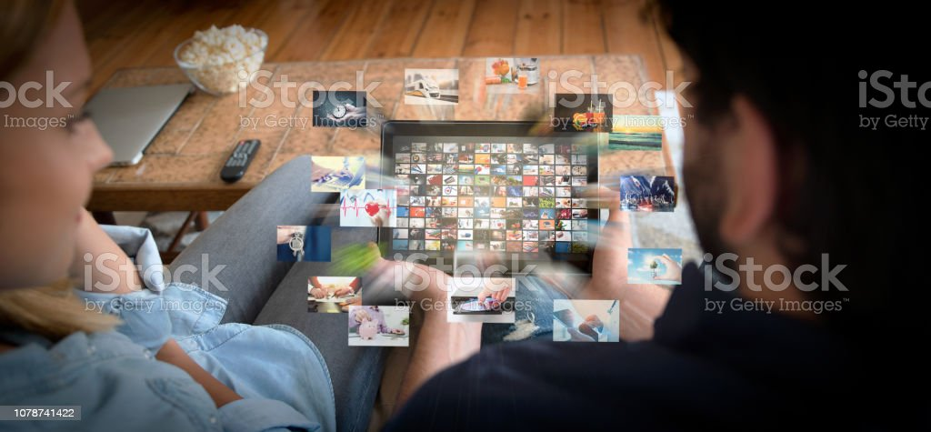 Couple using tablet for watching VOD service stock photo
