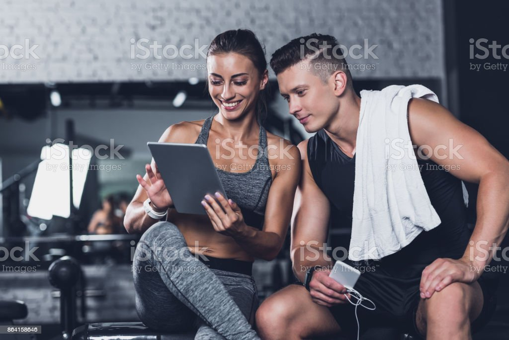 couple using tablet in gym royalty-free stock photo