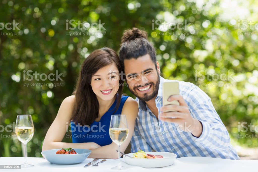 Couple using taking a selfie on mobile phone stock photo