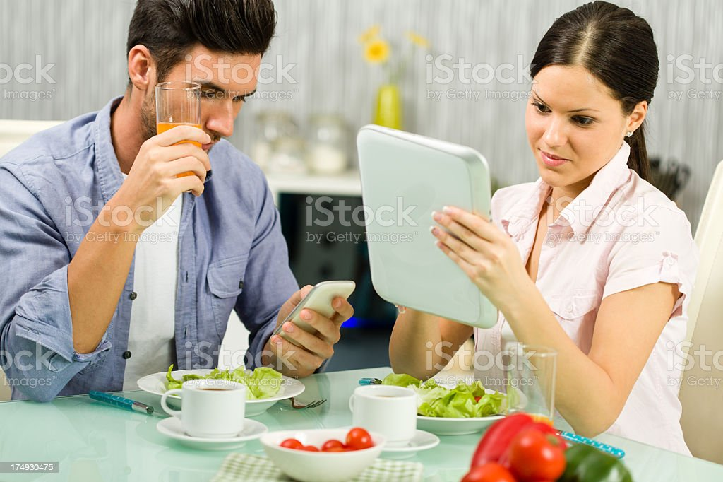 Couple using technology during lunch royalty-free stock photo