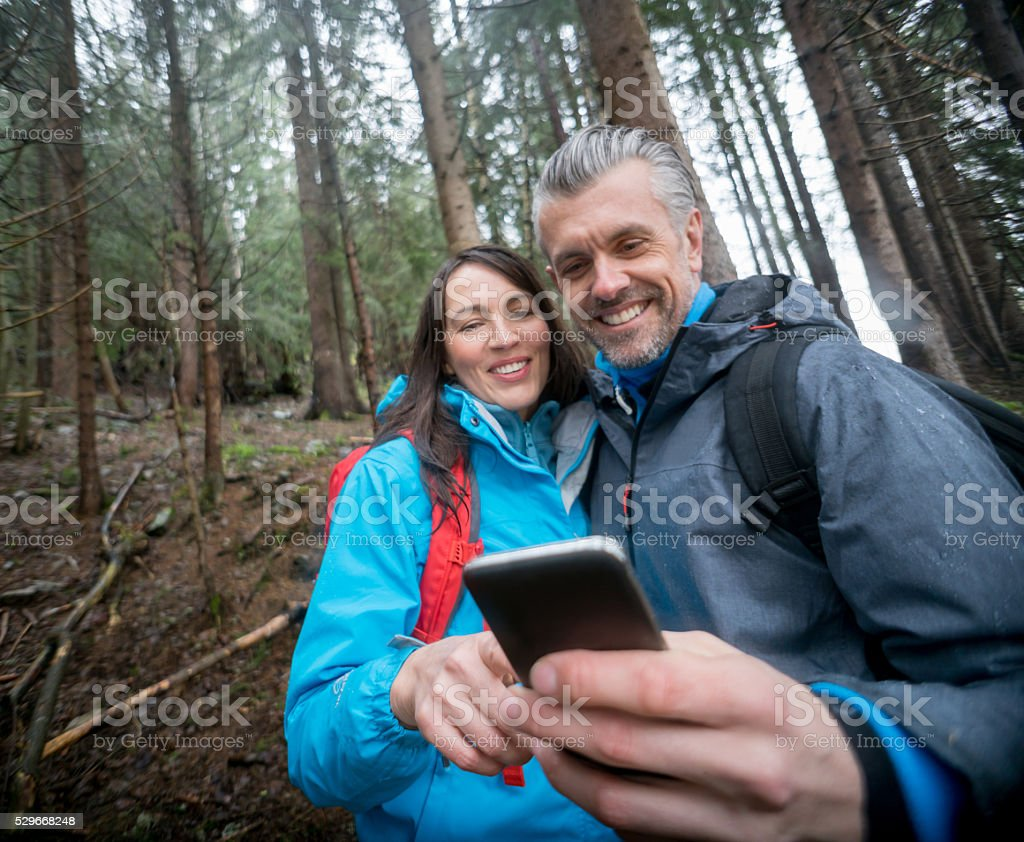 Couple using technology in the middle of nowhere stock photo