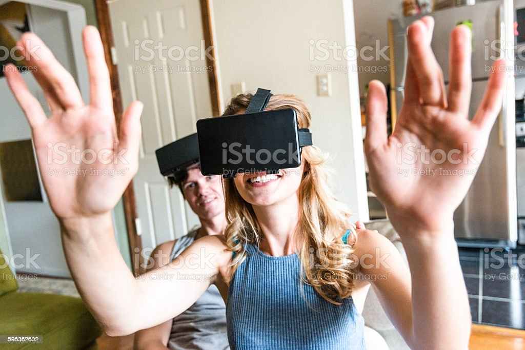 couple using the VR simulator at home on the sofa royalty-free stock photo