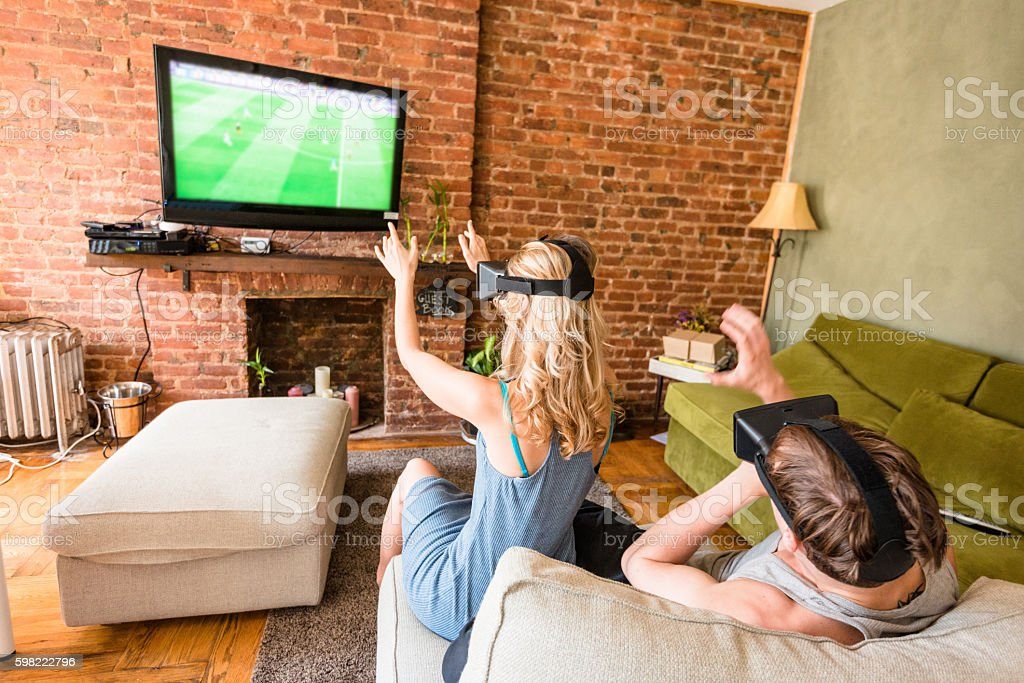 couple using the VR simulator at home on the sofa stock photo