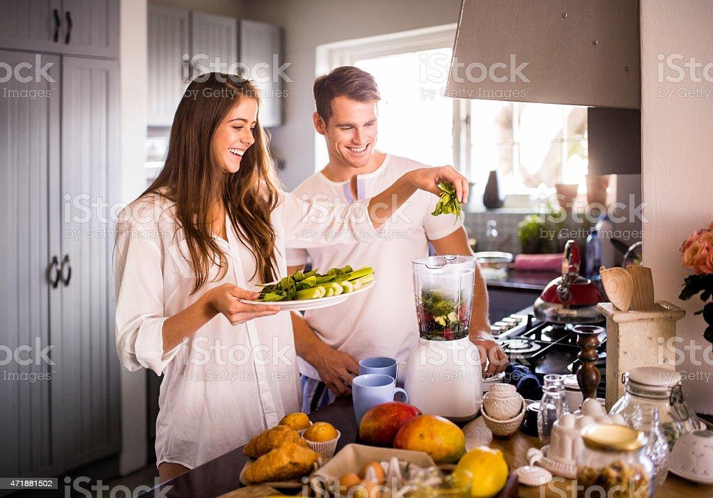 Couple à l'aide d'un mélangeur pour prendre un petit déjeuner équilibré - Photo
