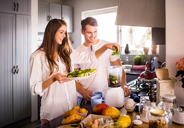 Couple using their blender to make a healthy breakfast Smiling couple using their blender togehter to make a fresh healthy breakfast blender stock pictures, royalty-free photos & images