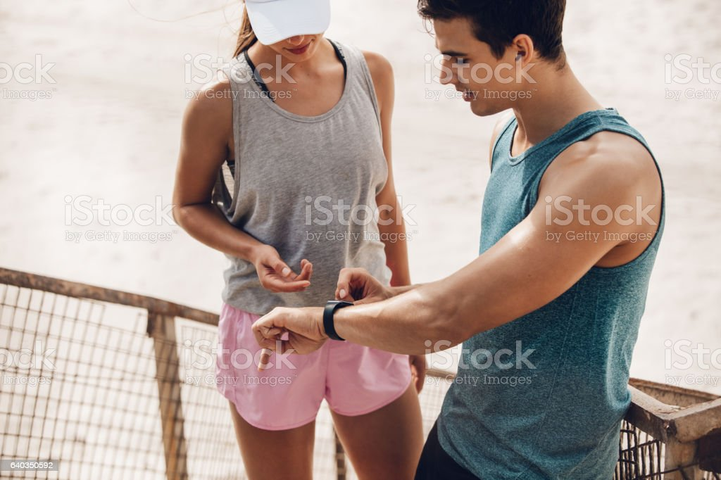 Couple using wearable technology during workout stock photo