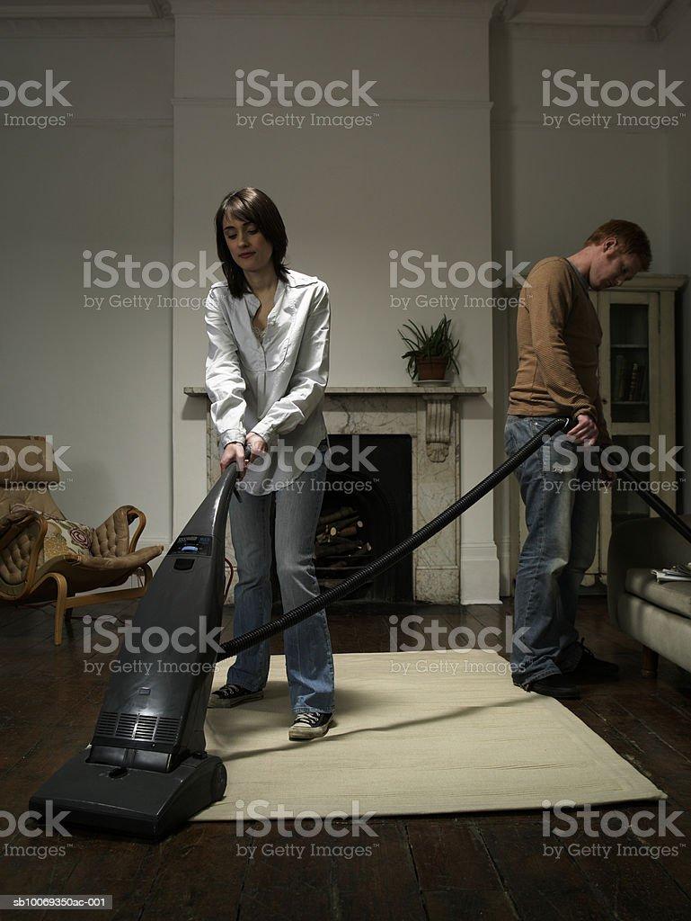Couple vacuuming living room royalty-free stock photo