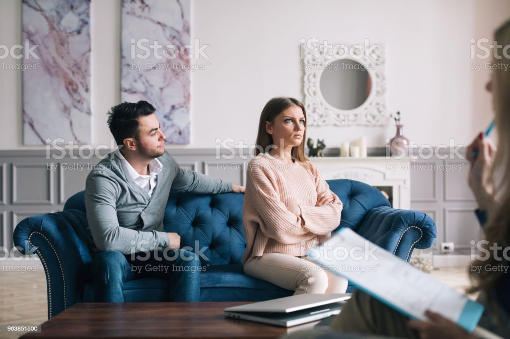 Couple visiting a psychologist and having a psychological session while dealing with problems in relationships. - Royalty-free Adult Stock Photo