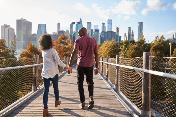 couple visiting new york with manhattan skyline in background - new york città foto e immagini stock