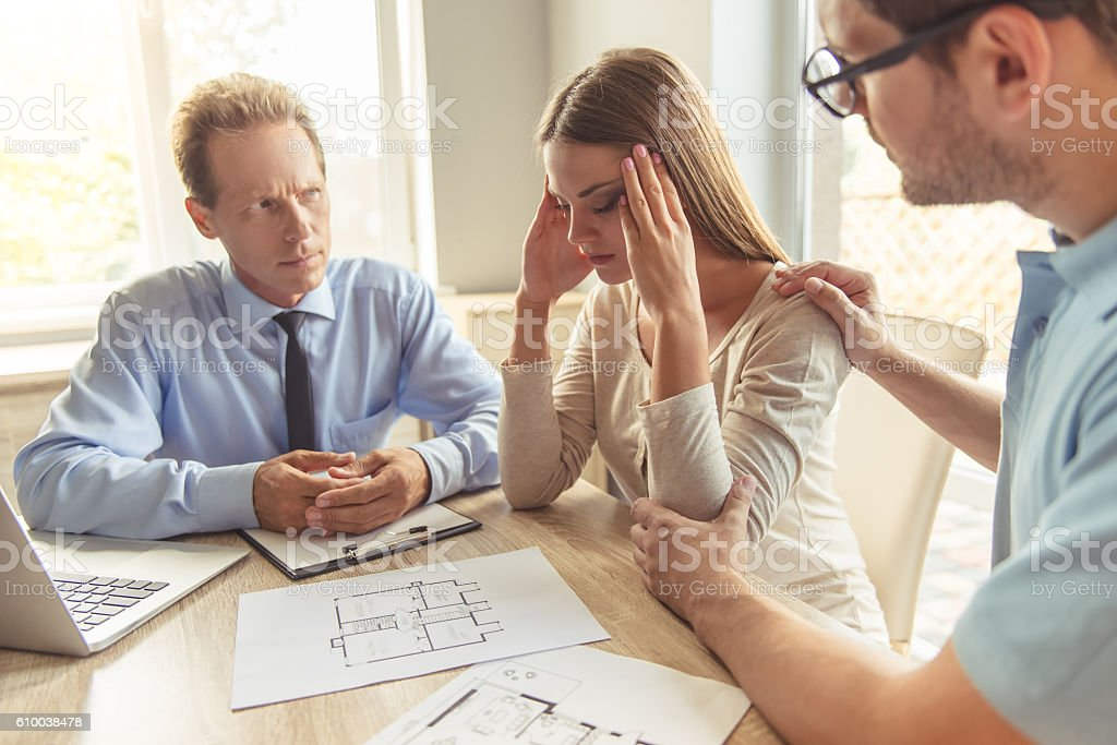 Couple visiting realtor Handsome middle aged realtor in classic shirt and young couple are discussing new house while sitting in office. Woman is having headache Adult Stock Photo