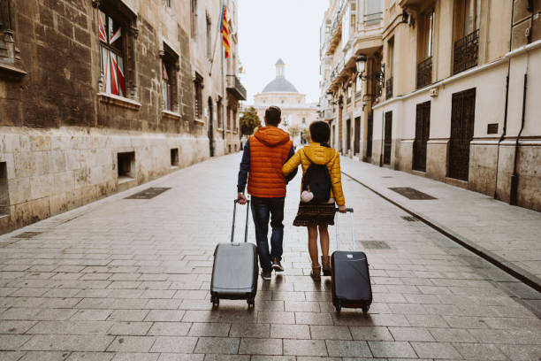 Couple visiting Valencia Rear view of couple arriving in Valencia early in the morning fresh start morning stock pictures, royalty-free photos & images