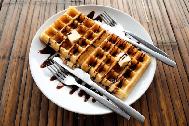 ein paar waffeln mit schokoladensauce, butter, löffel und gabel in weißer teller auf dem holztisch. - low carb kekse stock-fotos und bilder