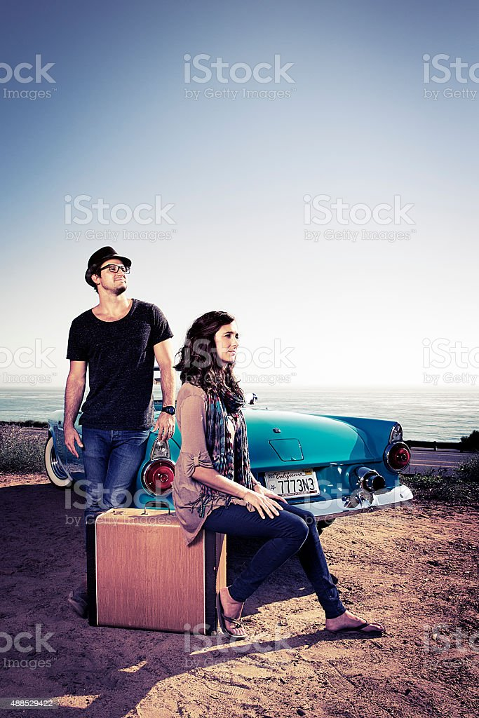 Couple Waiting by  a Blue Convertible stock photo