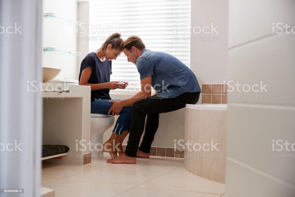 Pareja a la espera de resultado de prueba de embarazo casera en baño - foto de stock