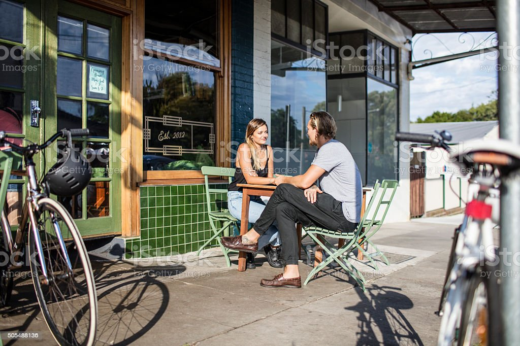 Couple waiting to be served at an sidewalk coffee shop stock photo