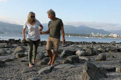 Couple walk along beach, tidal zone