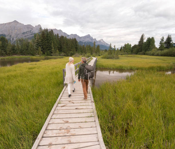 paar fuß entlang der promenade über marschland. - lange jacken stock-fotos und bilder