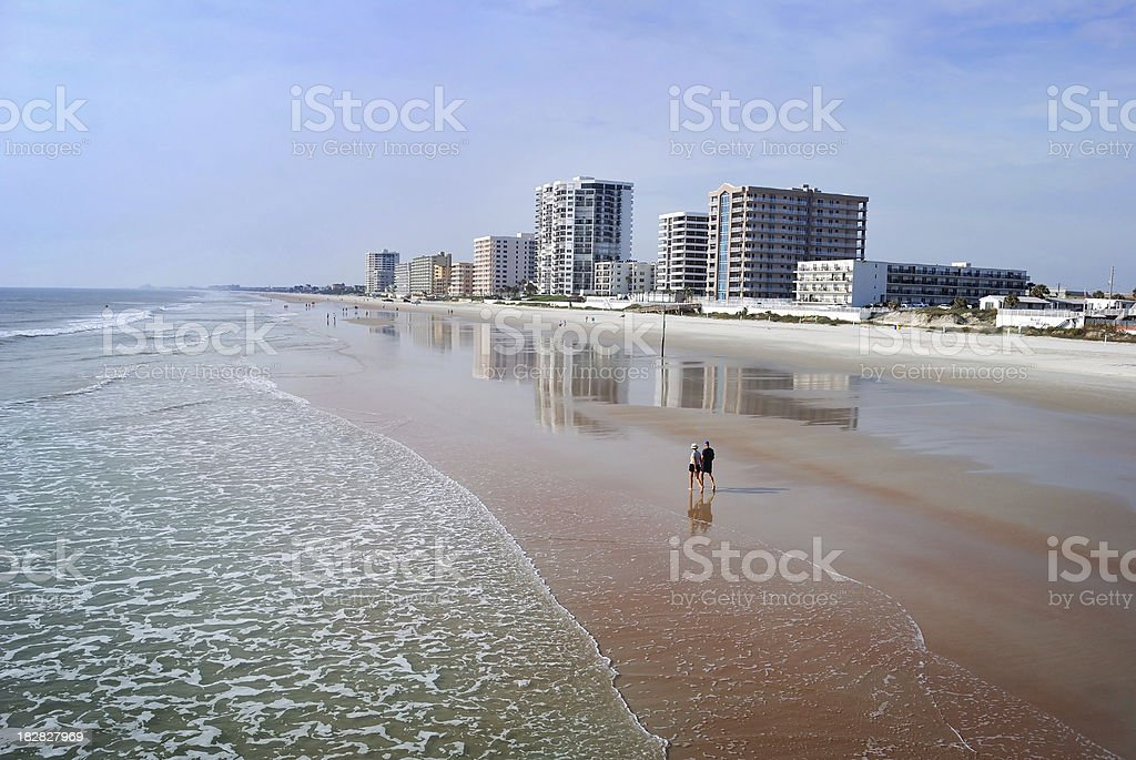 Couple Walk Along Daytona Beach Shores Florida Coastline of Condominiums stock photo