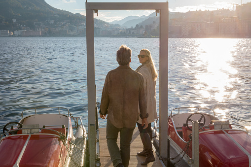Couple walk along dock on a sunny lake in the mountains